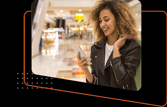 Mujer con celular en un centro comercial