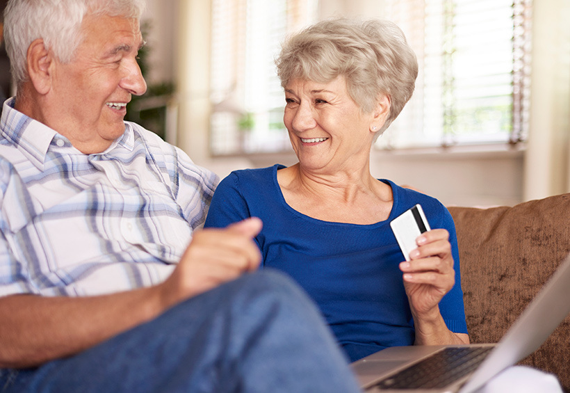 Adultos mayores con una tarjeta de crédito en la mano